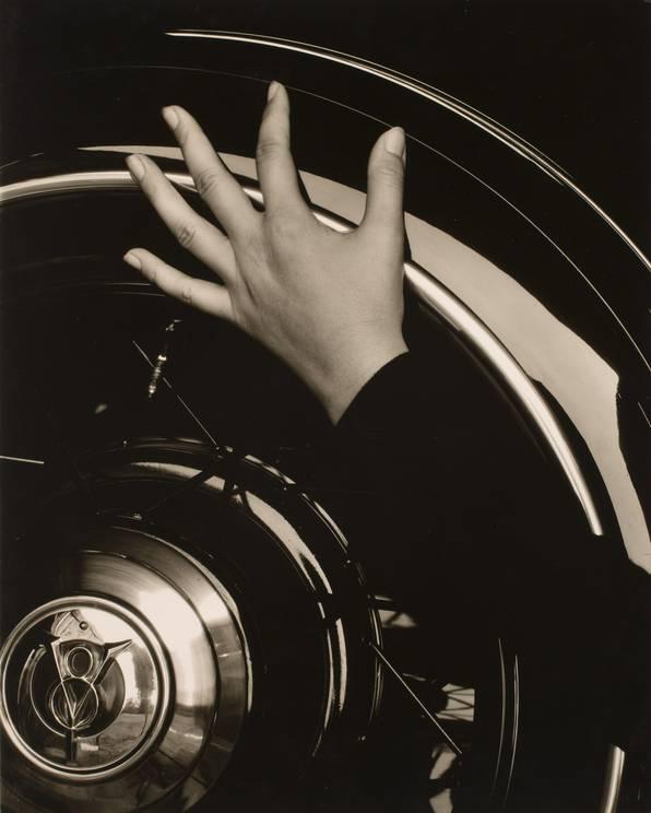 Alfred Stieglitz  - Georgia O'Keeffe, Hand on Back Tire of Ford V8 (1920)